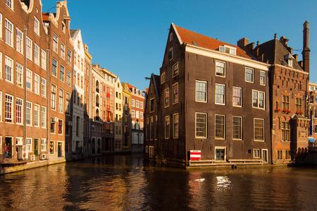 Traditionele Nederlandse gebouwen weerspiegelen op kanaal water bij zonsondergang