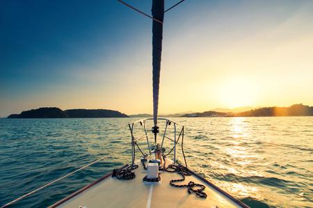 voile: Nez de yacht à voile dans la mer au coucher du soleil Banque d'images