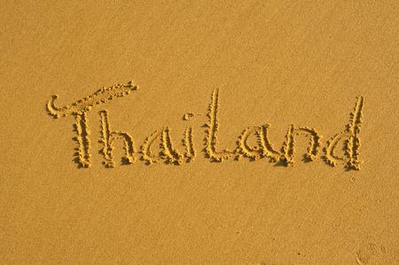 Woord Thailand geschreven op een natte strand