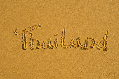 Word Thailand written on a wet sandy beach