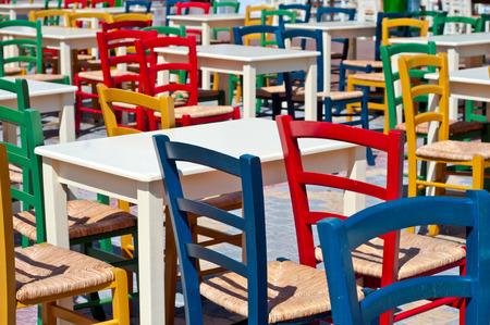Een foto van kleurrijke stoelen buiten een restaurant
