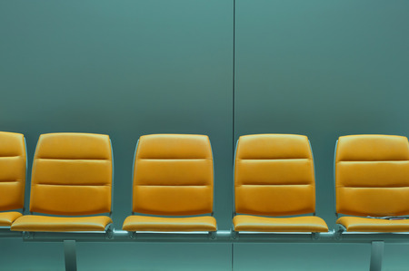 Row of empty chairs at airport waiting area Stock Photo