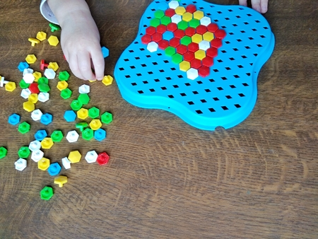child playing mosaic at the wooden table