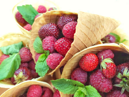 raspberries and strawberries with mint leaves in a waffle cone on a white background