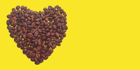 Heart of coffee beans on a yellow background. Copy space