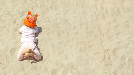 Baby in bright orange panama lies on a sandy beach. Copy space