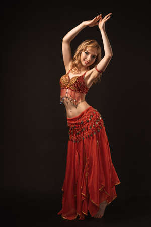 Young beautiful exotic eastern women performs belly dance in ethnic red dress on gray background. Studio shot art