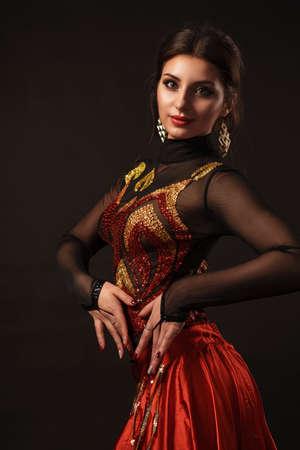 Hermosa bailarina de danza del vientre que realiza danza exótica en vestido rojo flutter art Foto de archivo