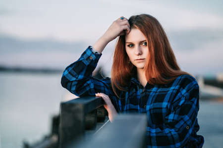 Serene girl standing alone on waterfront in front of fence of embankment art.