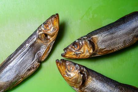 three smoked sprat fish on a green cutting board