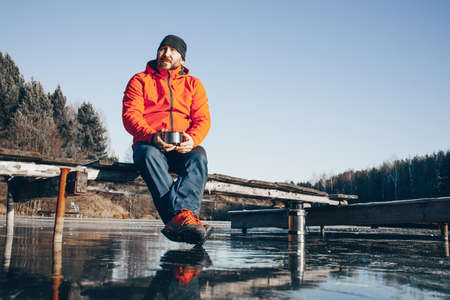 A lone tramp traveler stands on ice and drinks tea from a thermo