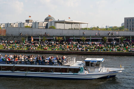 residents: BERLIN, GERMANY - APRIL 19, 2014: Restaurant on the embankment Spree and pleasure boat. Traditional pastime visitors and residents of of Berlin. Editorial