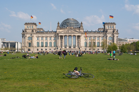 vacationers: BERLIN, GERMANY - APRIL 19, 2014: The Reichstag building and vacationers residents and visitors on the field. The Reichstag building is a historical edifice in Berlin.  Editorial