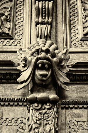 heads old building facade: Woodcarving. Decoration vintage gate of the Old Town Hall. Sepia. Prague.