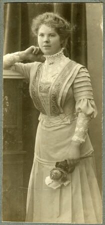 grandfather clock: BERLIN, GERMANY - CIRCA 1905: A vintage portrait of young woman, standing near the grandfather clock and a flower in her hand, circa 1905