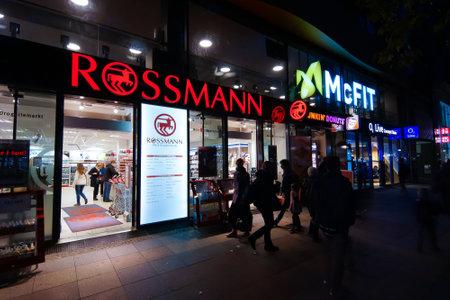 retail chain: BERLINO, GERMANIA - 17 ottobre 2014: Drugstore Rossmann in illuminazione notturna. Rossmann - � la pi� grande catena di farmacia di vendita al dettaglio della Germania, 1.900 filiali e 28.000 dipendenti.