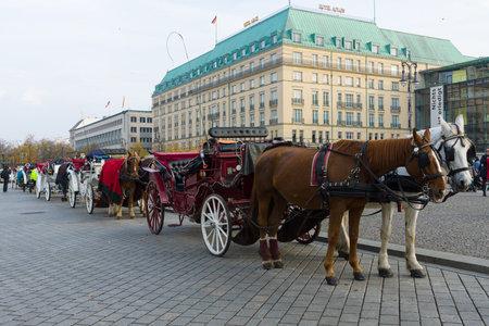 the coachman: BERLIN - OCTOBER 31, 2014: Coaches on the Pariser Platz, in the background the famous luxury Hotel Adlon Kempinski