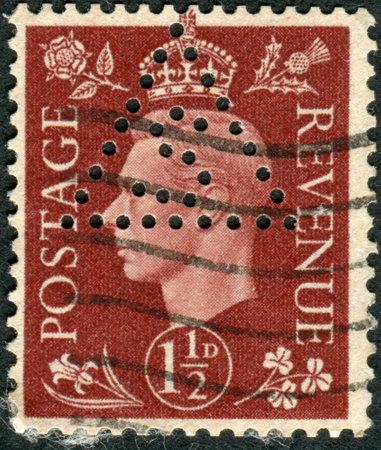 dominions: UNITED KINGDOM - CIRCA 1937: Postage stamp printed in England (Perfin S in a triangle), shows King of the United Kingdom and the Dominions of the British Commonwealth, George VI, circa 1937