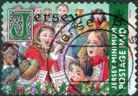 dependencies: JERSEY - CIRCA 2001: Postage stamp printed in Jersey (Crown dependencies of the British Crown), Christmas Issue, shows children sing Christmas songs, circa 2001