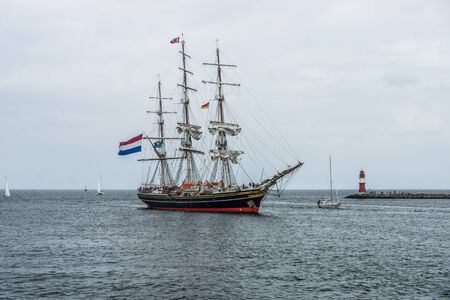ROSTOCK, GERMANY - AUGUST 02, 2014: Three-masted Dutch clipper Stad Amsterdam (City of Amsterdam) enters the harbor of Rostock, Warnemuende district. Toning Editorial