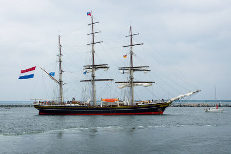 enters: ROSTOCK, GERMANY - AUGUST 02, 2014: Three-masted Dutch clipper Stad Amsterdam (City of Amsterdam) enters the harbor of Rostock, Warnemuende district. Editorial