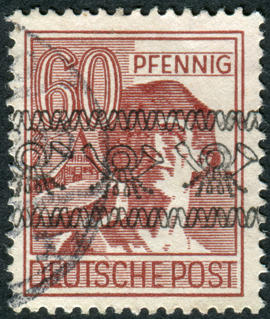 obliteration: GERMANY - CIRCA 1947: Postage stamp printed in Germany (overpint Type A: US and British occupation zone), shows the laborer, circa 1947 Editorial