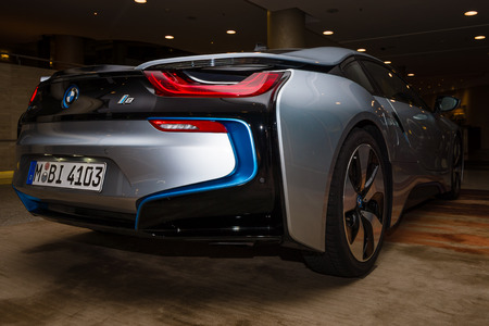 BERLIN - NOVEMBER 28, 2014: Showroom. The BMW i8, first introduced as the BMW Concept Vision Efficient Dynamics, is a plug-in hybrid sports car developed by BMW. Rear view.