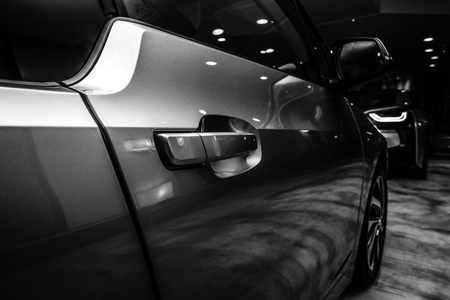 i3: BERLIN - NOVEMBER 28, 2014: Showroom. A fragment of the BMW i3, previously Mega City Vehicle (MCV), is a five-door urban electric car developed by the German manufacturer BMW. Black and white.