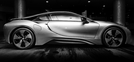 silver sports car: BERLIN - NOVEMBER 28, 2014: Showroom. The BMW i8, first introduced as the BMW Concept Vision Efficient Dynamics, is a plug-in hybrid sports car developed by BMW. Black and white.