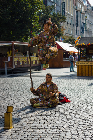 levitation: PRAGUE, CZECH REPUBLIC - SEPTEMBER 18, 2014: Performance of street artists on Wenceslas Square. Imitation of levitation.