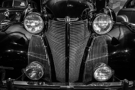 car grill: MAASTRICHT, NETHERLANDS - JANUARY 08, 2015: Radiator grill and headlamps of a full-size luxury car Cadillac Series 75 Imperial Sedan, 1939, close-up. Black and white. International Exhibition InterClassics & Topmobiel 2015 Editorial