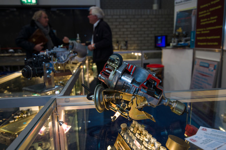 distributor: MAASTRICHT, NETHERLANDS - JANUARY 09, 2015: Stand of the firm for the sale of spare parts for oldtimers. In the foreground is the distributor of ignition. International Exhibition InterClassics & Topmobiel 2015 Editorial