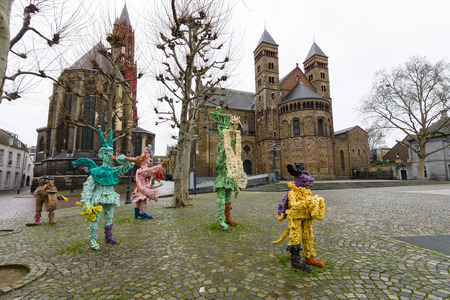 t square: MAASTRICHT, NETHERLANDS - JANUARY 09, 2015: Vrijthof square. People and animals in stone and bronze (t Zaat Herremenieke) by Han van Wetering. Sculpture dedicated to the carnival. In the background Evangelical Church of St. John and Basilica of St. Serva Editorial