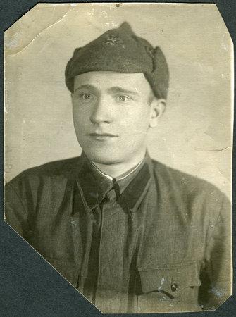 cloth cap: KIEV, USSR - CIRCA 1941: Portrait of a Red Army soldier in Budyonovka (cloth cap  helmet), circa 1941