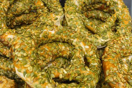 sprinkled: Fresh a bagel sprinkled with pumpkin seeds. Background. Stock Photo