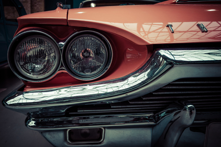 stylization: BERLIN - MAY 10, 2015: Headlamp of a large personal luxury car Ford Thunderbird 390 Coupe (second generation), 1964. Stylization. Vintage toning. 28th Berlin-Brandenburg Oldtimer Day