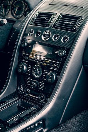 v8: BERLIN - JUNE 14, 2015: Fragment of the dashboard of a luxury sports car Aston Martin V8 Vantage N430 (since 2015). Toning. Stylization. The Classic Days on Kurfuerstendamm.