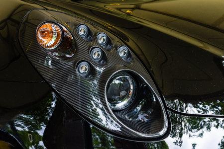 alfa: BERLIN - JUNE 14, 2015: Headlamp of the sports car Alfa Romeo 4C (since 2014). The Classic Days on Kurfuerstendamm.