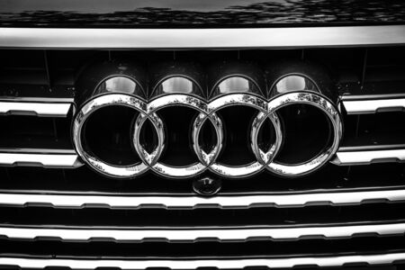 car grill: BERLIN - JUNE 14, 2015: The emblem on the front grille of a full-size luxury crossover SUV Audi Q7 3.0 TDI quattro. Black and white. The Classic Days on Kurfuerstendamm.