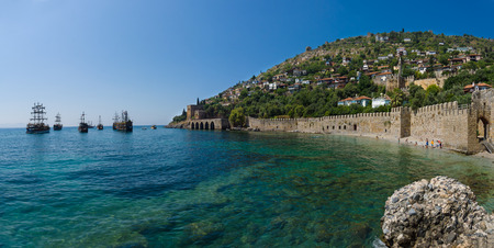 Shipyard (Tersane) and the ruins of a medieval fortress (Alanya Castle) on the mountainside.  Stock Photo