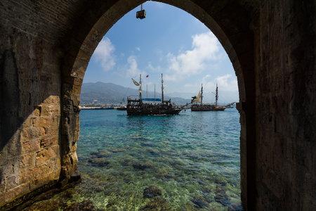 pirata: Alanya, Turqu�a - 04 de julio 2015: Mar Mediterr�neo. Complejo de entretenimiento tradicional de Alanya. Navegando buques aka piratas alrededor de la fortaleza de Alanya. Vista desde el astillero (Tersane) y las ruinas de una fortaleza medieval (Castillo de Alanya).