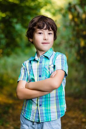 Ironic portrait of a boy with arms folded.