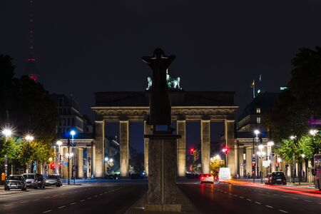 caller: BERLIN, GERMANY - OCTOBER 13, 2015: A view of the Brandenburg Gate from the 17th of June Street. In the foreground, a sculpture Der Rufer (The Caller)