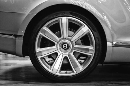 braking: BERLIN - AUGUST 31, 2012: Showroom. Wheels and braking system components of a full-size luxury car Bentley New Continental GT V8 convertible. Black and white. Close-up. Produced since 2013.