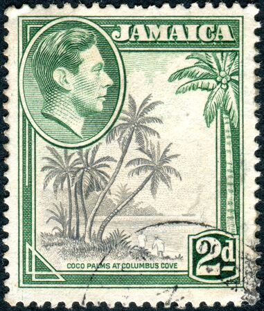jamaica: JAMAICA - CIRCA 1938: Postage stamp printed in Jamaica, shows a portrait of King George VI and Coco Palms at Columbus Cove, circa 1938