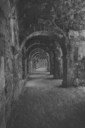 passages: Internal passages in the ancient Roman amphitheater of Aspendos. The province of Antalya. Mediterranean coast of Turkey. Black and white. Stylization. Stock Photo