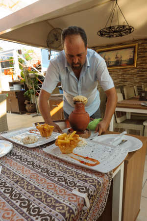 clay pot: SIDE, TURKEY - JULY 07, 2015: The restaurant in Side, the waiter served the meat from the clay pot.