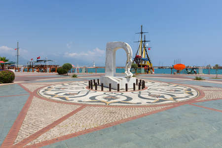 alanya: ALANYA, TURKEY - JULY 09, 2015: Monument and pleasure boats in the sea port of Alanya. Alanya - a popular holiday destination for European tourists.
