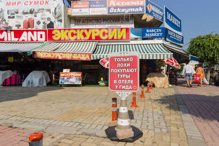 guides: KONAKLI, TURKEY - JULY 10, 2015: Outdoor advertising sightseeing tours. In the foreground of advertising in Russian: Only losers are buying tour guides at the hotel. Editorial