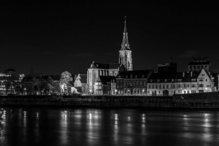 maas: MAASTRICHT, NETHERLANDS - JANUARY 16, 2016: City in the night. Maas River in the foreground. Black and white. Maastricht is the oldest city of the Netherlands and the capital city of the province of Limburg.